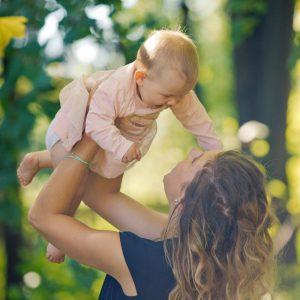 Fotografin Baby wird Überkopf gehalten und lacht dabei seine Mutter an