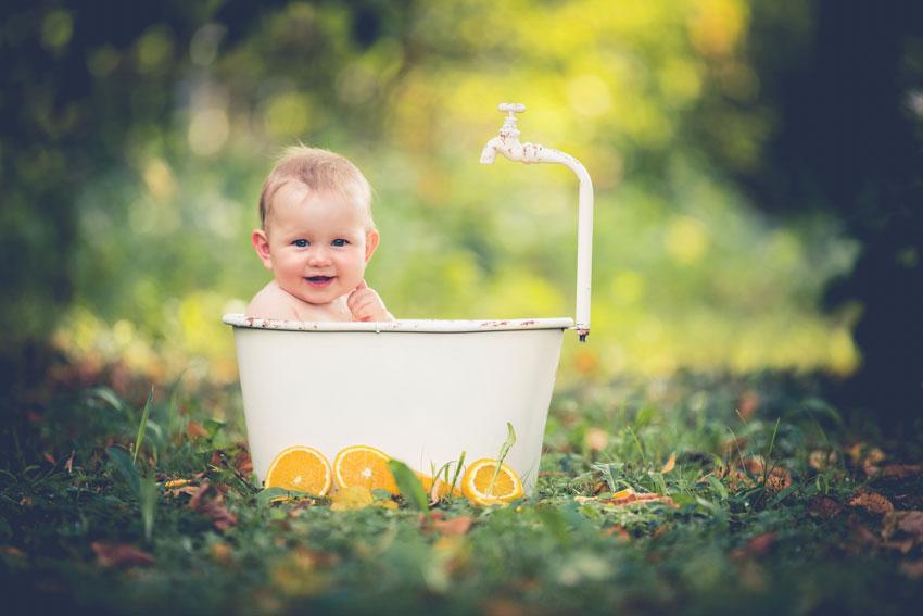 Baby sitzt lächelnd in einer alten kleinen Badewanne im Freien