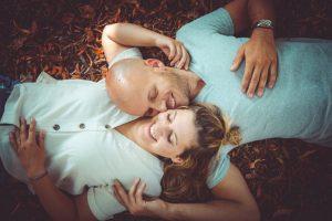 Paar im Herbstlaub am Boden liegend
