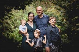 Familie mit drei Kindern im Park vor grünem Hintergrund