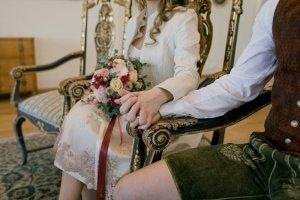 Brautpaar am Standesamt hält Händchen in Lederhose bei der Hochzeit