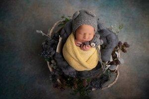 Neugeborenes in gelbem Wrap gewickelt mit grauem Stoffteddy in den Händen und umringt von blauen Blüten